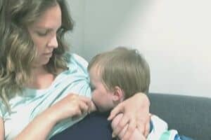 toddler nursing with pregnant mother